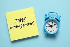 蓝色闹钟和纸提示 时间管理、优先权、效率、控制和目标 库存图片