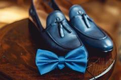 蓝色鞋子和蝶形领结在一把木圆的凳子 礼服的辅助部件 高雅和时尚的标志人的 免版税图库摄影