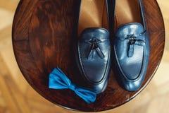 蓝色鞋子和蝶形领结在一把木圆的凳子 礼服的辅助部件 高雅和时尚的标志人的 库存照片