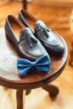 蓝色鞋子和蝶形领结在一把木圆的凳子 礼服的辅助部件 高雅和时尚的标志人的 图库摄影