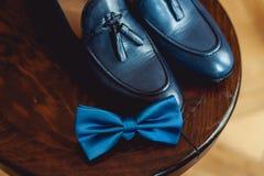蓝色鞋子和蝶形领结在一把木圆的凳子 礼服的辅助部件 高雅和时尚的标志人的 免版税库存图片