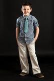 蓝色领带的窃笑的男孩 免版税库存图片