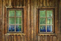 蓝色颜色botles在老窗口里 免版税库存图片
