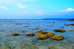 蓝色风景-在多岩石的海滩和天空的干净的海水-自然本底- Laxmanpur,尼尔海岛,安达曼尼科巴,印度 免版税库存照片