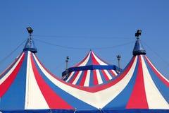 蓝色马戏五颜六色的天空镶边帐篷下 免版税库存照片