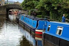 蓝色驳船被停泊对一条运河的银行在英国 库存照片