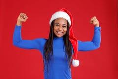 蓝色高尔夫球和圣诞节帽子的一个愉快的非裔美国人的女孩显示她的手的二头肌和微笑着 图库摄影
