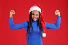 蓝色高尔夫球和圣诞节帽子的情感非裔美国人的女孩显示二头肌手和握紧的牙 库存照片