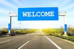 蓝色高速公路在与词欢迎o的晴天签署路 免版税库存图片