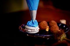 蓝色黄油奶油的应用与一个烹调袋子的在灰色macaron 免版税库存图片