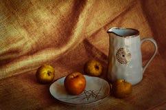 蓝色黏土水罐和一块大陶瓷板材在粗糙的粗麻布 苹果滚动了下来桌 r 油漆的温暖的颜色 免版税库存照片