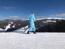 蓝色,桃红色独角兽睡衣kigurumi的女孩室外与在滑雪报告的雪板在雪山 库存图片