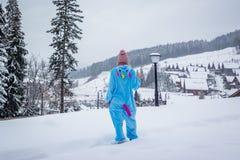 蓝色,桃红色独角兽pijama kigurumi的女孩室外在滑雪报告的木屋前面在雪山 免版税库存图片