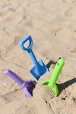 蓝色,绿色和紫色海滩铁锹在沙子黏附了在晴朗 库存图片