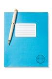 蓝色练习本和笔 免版税库存图片