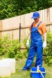 蓝色总体的工匠和橙色T短的看的油漆罐和桶 免版税库存图片