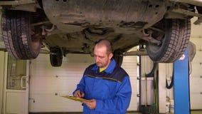 蓝色总体的汽车机械师根据在garge的汽车检查填装纸 股票视频