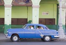 蓝色经典古巴汽车和被毁坏的修造 免版税库存照片