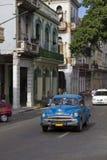 蓝色经典驾车在老古巴街道下 免版税库存照片