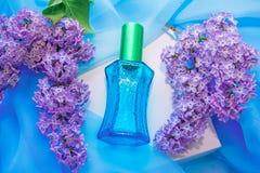 蓝色玻璃香水瓶和丁香花 图库摄影
