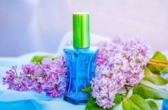 蓝色玻璃香水瓶和丁香花 免版税图库摄影