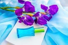 蓝色玻璃香水瓶和虹膜花 库存图片