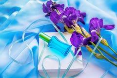 蓝色玻璃香水瓶和虹膜花 库存照片
