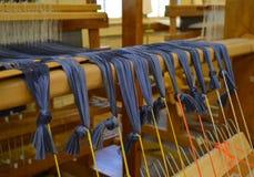 蓝色紫色在一台传统织机穿线 免版税库存图片
