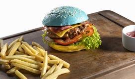 蓝色黄色汉堡和炸薯条在木板 免版税库存图片
