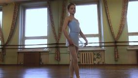 蓝色紧身连衣裤的女孩和准备好蓝色芭蕾舞短裙把柄的裙子做exrcises在芭蕾舞蹈艺术期间在磨损分类 股票录像