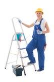蓝色建造者制服的少妇画家有梯子和工具的 免版税库存图片