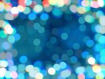 蓝色bokeh defocused背景 光亮发光的色的五彩纸屑,被弄脏的背景框架  免版税库存图片
