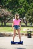 蓝色hoveboard的十几岁的女孩 库存图片