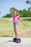 蓝色hoverboard的十几岁的女孩 免版税库存图片