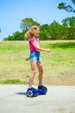 蓝色hoverboard的十几岁的女孩 免版税库存照片