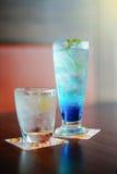 蓝色itallian在一块玻璃的苏打被冰的和饮用水在木桌,在绿色叶子的选择聚焦,被过滤的图象上 免版税图库摄影