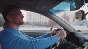 蓝色longsleeve的白人与在面孔的微笑驾驶有大厦和其他汽车的汽车在背景 影视素材