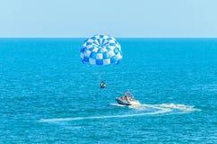 蓝色parasail翼乘在海水,帆伞运动的一条小船拉扯了 免版税库存照片