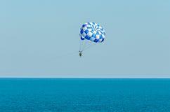 蓝色parasail翼乘在海水, Parasailin的一条小船拉扯了 免版税库存图片