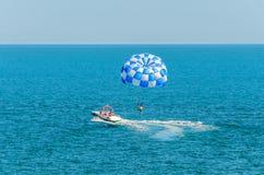 蓝色parasail翼乘在海水, Parasailin的一条小船拉扯了 免版税图库摄影