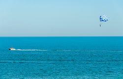 蓝色parasail翼乘在海水, Parasailin的一条小船拉扯了 免版税库存照片