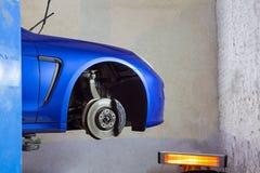 蓝色sportcar在轮胎和轮子replacem的服务站 免版税库存照片
