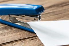 蓝色stepler和纸在木背景覆盖 库存图片