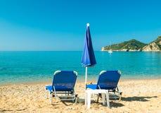 蓝色sunbeds和蓝色伞在海滩在科孚岛海岛,希腊 免版税图库摄影