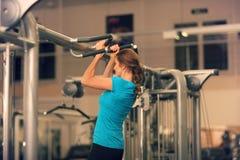 蓝色T恤杉和黑裤子的坚强的妇女行使在健身房-做的引体向上 库存图片