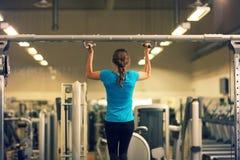 蓝色T恤杉和黑裤子的坚强的妇女行使在健身房-做的引体向上 免版税库存照片