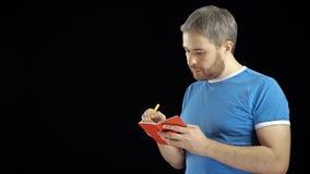 蓝色T恤杉文字的英俊的人在他的红色笔记本 备忘录、查寻或者联络概念 黑色背景 4K录影 股票录像