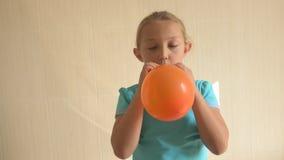 蓝色T恤杉的愉快的女孩在卫生间里在家膨胀一个明亮的橙色球 浅的重点 股票录像