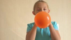 蓝色T恤杉的愉快的女孩在卫生间里在家膨胀一个明亮的橙色球 浅的重点 股票视频