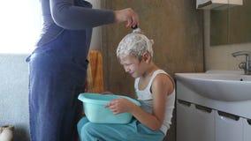 蓝色T恤杉的愉快的女孩在卫生间里在家膨胀一个明亮的橙色球 浅的重点 影视素材